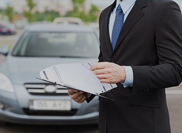 man with a suit holding a checklist next to a car
