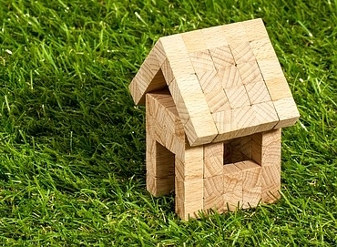 model of a wooden house on a grass