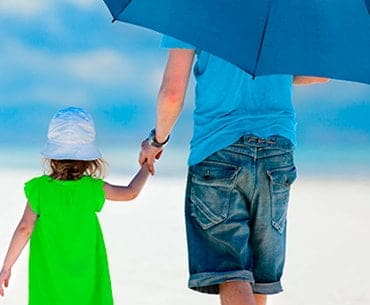 man with a daughter at a beach holding an umbrella