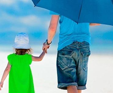 man with a daughter at a beach holding an umbrella